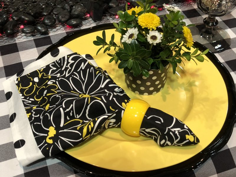 Colorful yellow and black table setting with flowers, make a house a home!