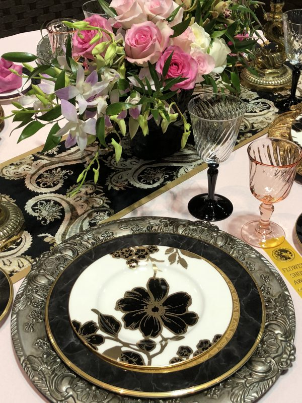 Elegant pink, black ans silver table setting with pink roses for accent.