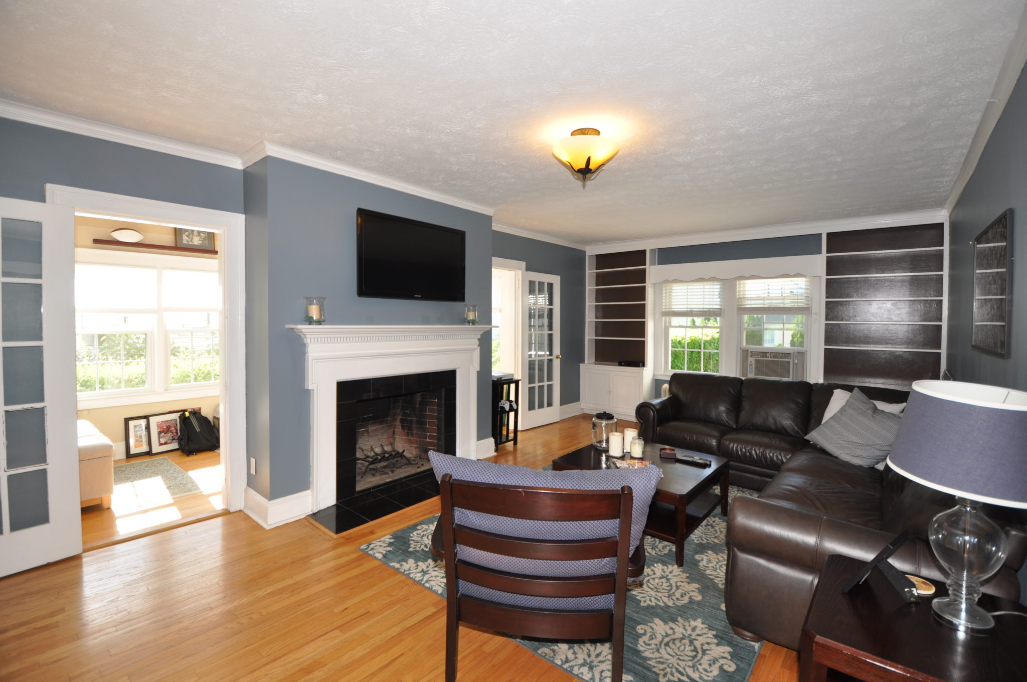 Spacious living room at 328 Fern St., West Hartford, Ct. Double French Doors to sunroom/office. Beautiful fireplace, gleaming hardwood floors, builtin bookcases.